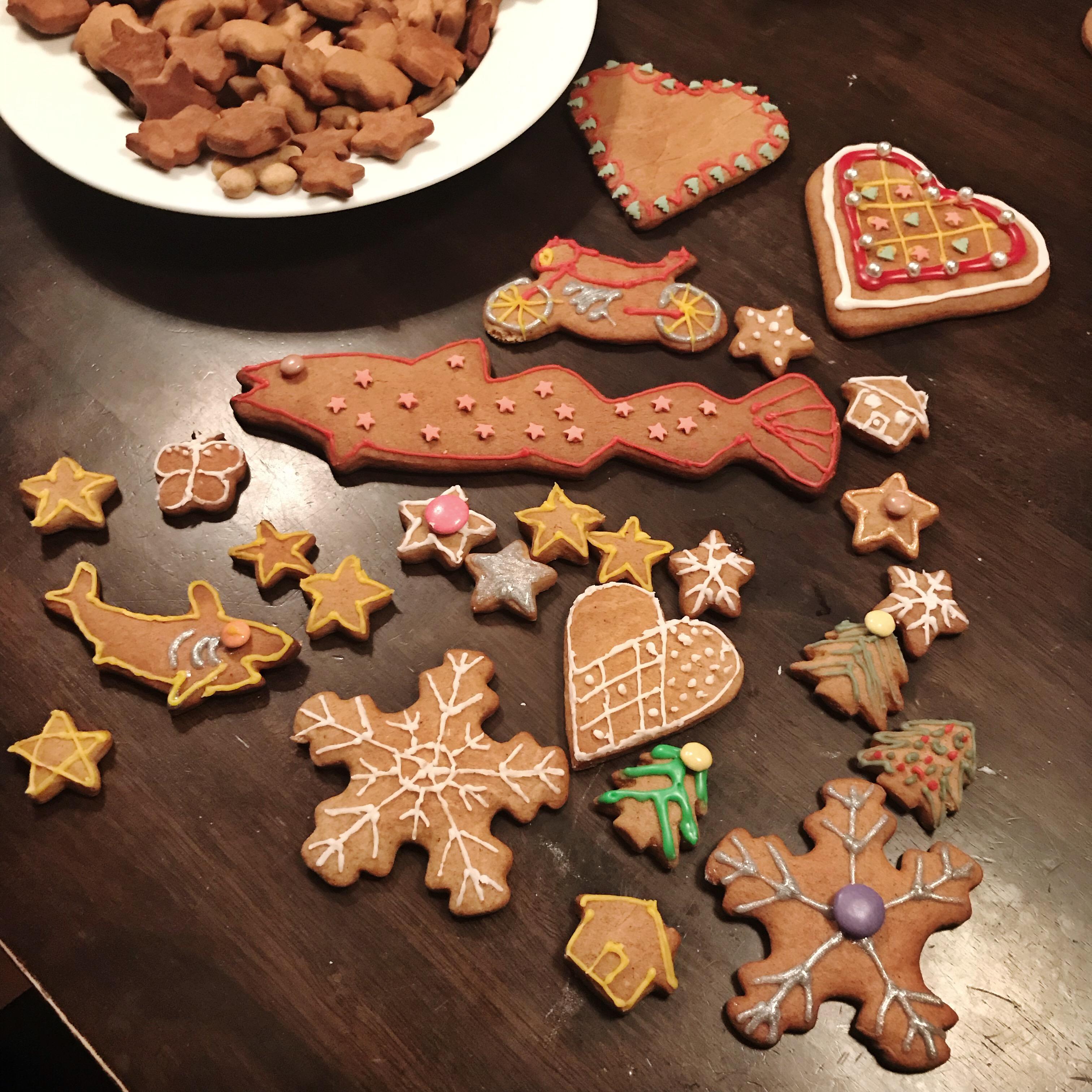 Mange pepperkaker i forskjellige former ligger på et bord. De er pyntet med glasur i flere farger.