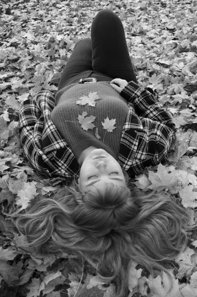 Et svart-hvitt bilde hvor Margrete ligger på bakken, som er dekt med høstblader. Hun har øynene lukket. Hun har på seg en rutete jakke, og håret ligger spredt utover bakken som en vifte.